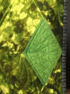 a very close up photo of quilting in a green diamond shaped block