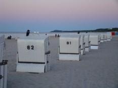 Krähen erobern die verlassenen Strandkörbe am Abend