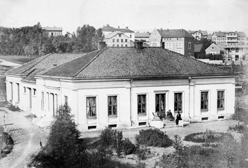 Residencia de profesores en el Jardín de la Universidad de 1864, se puede  observar a Peter Waage con un sombrero de copa
