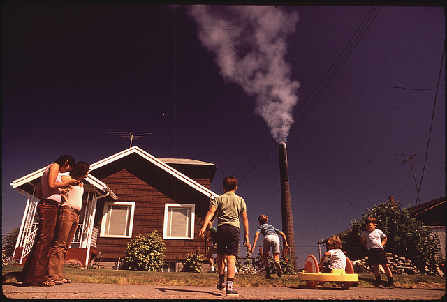 Original Caption: Children Play in Yard of Ruston Home, While Tacoma Smelter Stack Showers Area with Arsenic and Lead Residue, 08/1972.  Photographer: Gene Daniels