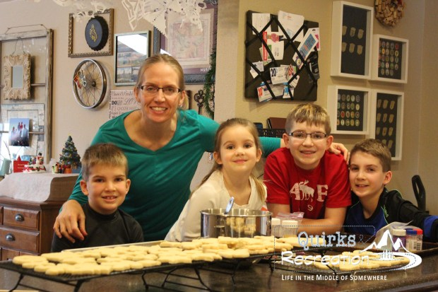 mother baking cookies with four children
