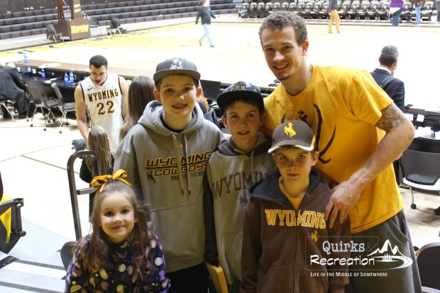 Children posing with Wyoming basketball player Josh Adams