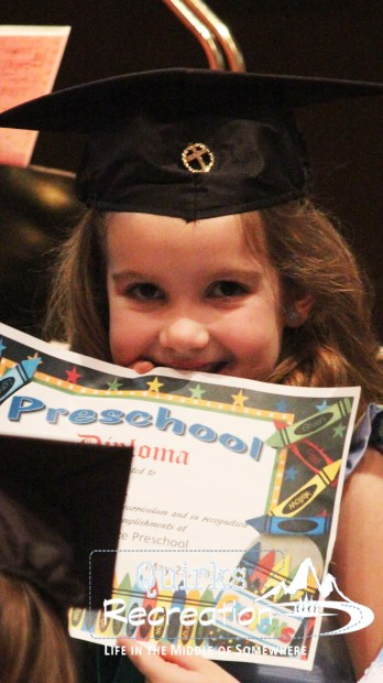 girl holding preschool diploma