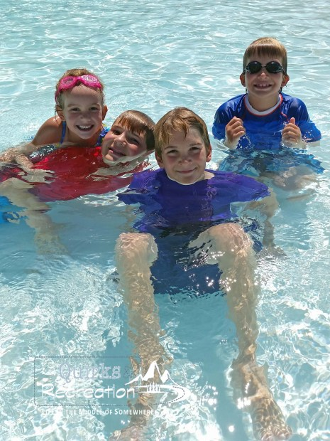 four children in the blue water of a swimming pool