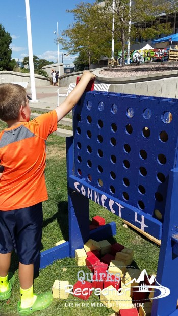 boy playing Connect 4 on an upycled pallet game board