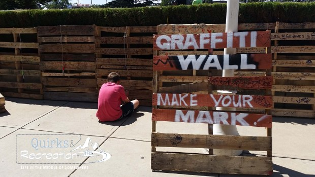 boy drawing on a pallet wall at Pallet Fest Denver
