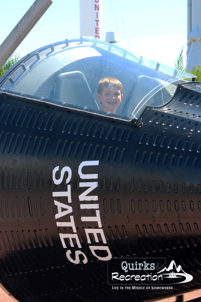 teen sitting in a rocket capsule at Kennedy Space Center