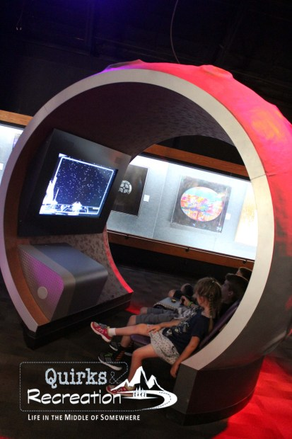 children sitting in a simulator at Kennedy Space Center