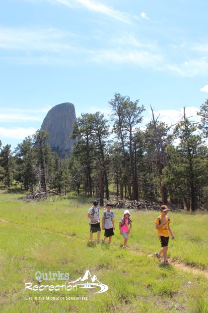 children hiking with Devils Tower National Monument in the background