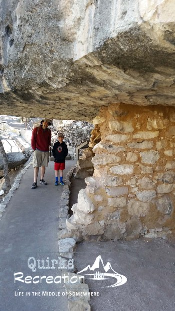 Two visitors standing near cliff dwellings at Walnut Canyon