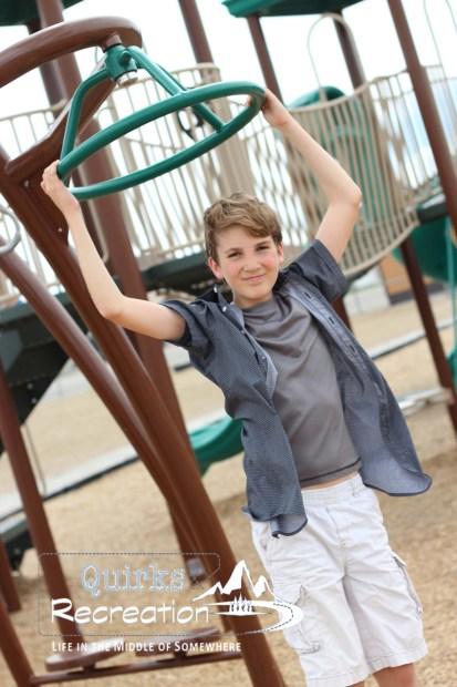 5th grade boy swining on playground equipment