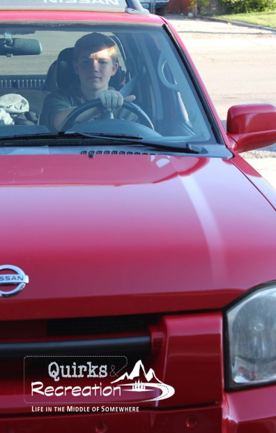 teenage boy driving red truck