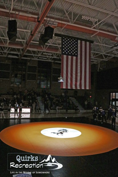 American flag hanging over a wrestling mat