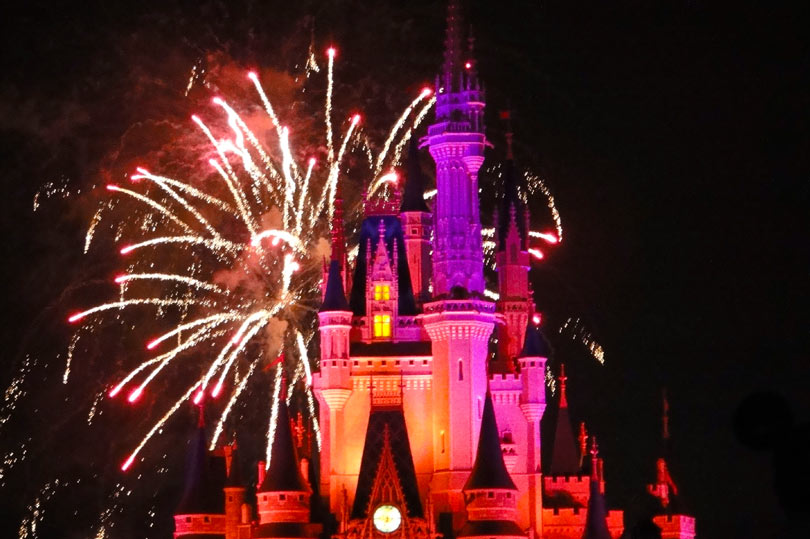 Disney castle lit up pink during the fireworks display at Magic Kingdom, Orlando, Florida