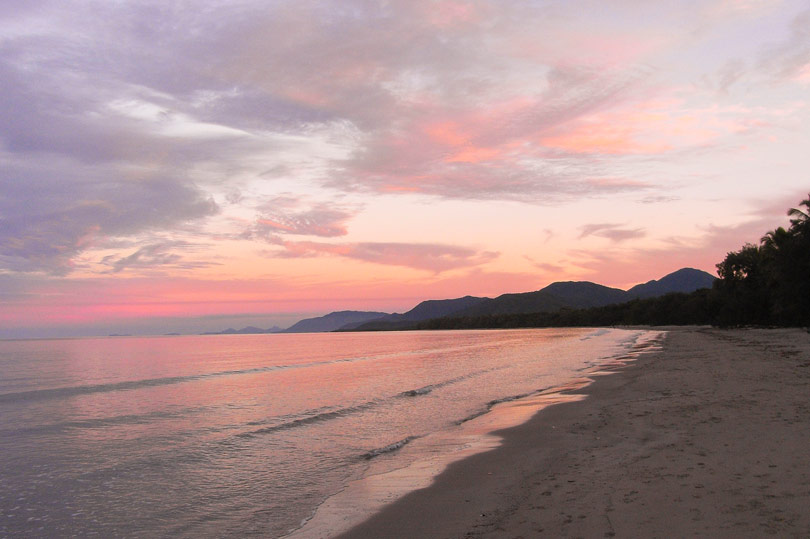 Soft candy coloured hues of the sun setting on Four Mile Beach in Port Douglas, Australia.