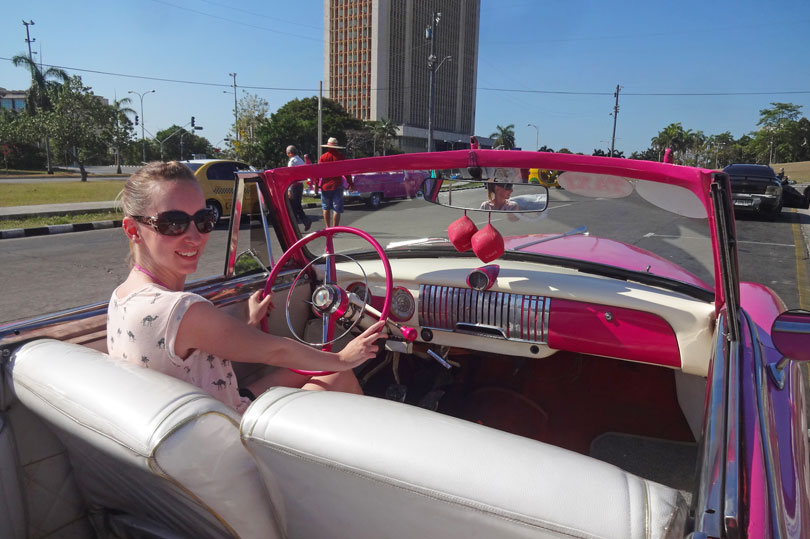 Posing in a 1952 pink Chevrolet at Revolution Square in Havana, Cuba