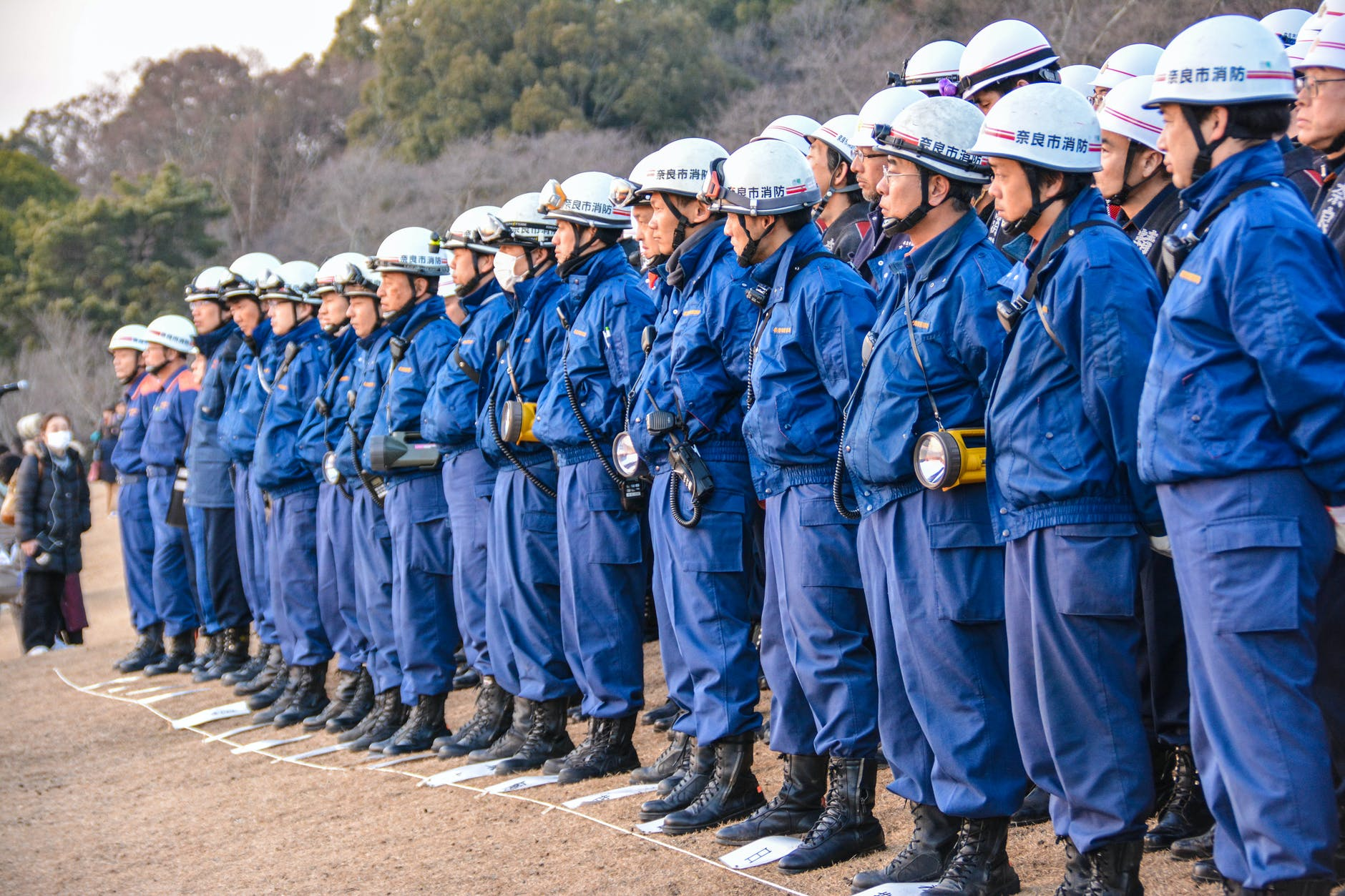 people in blue uniform standing on gray dirt road