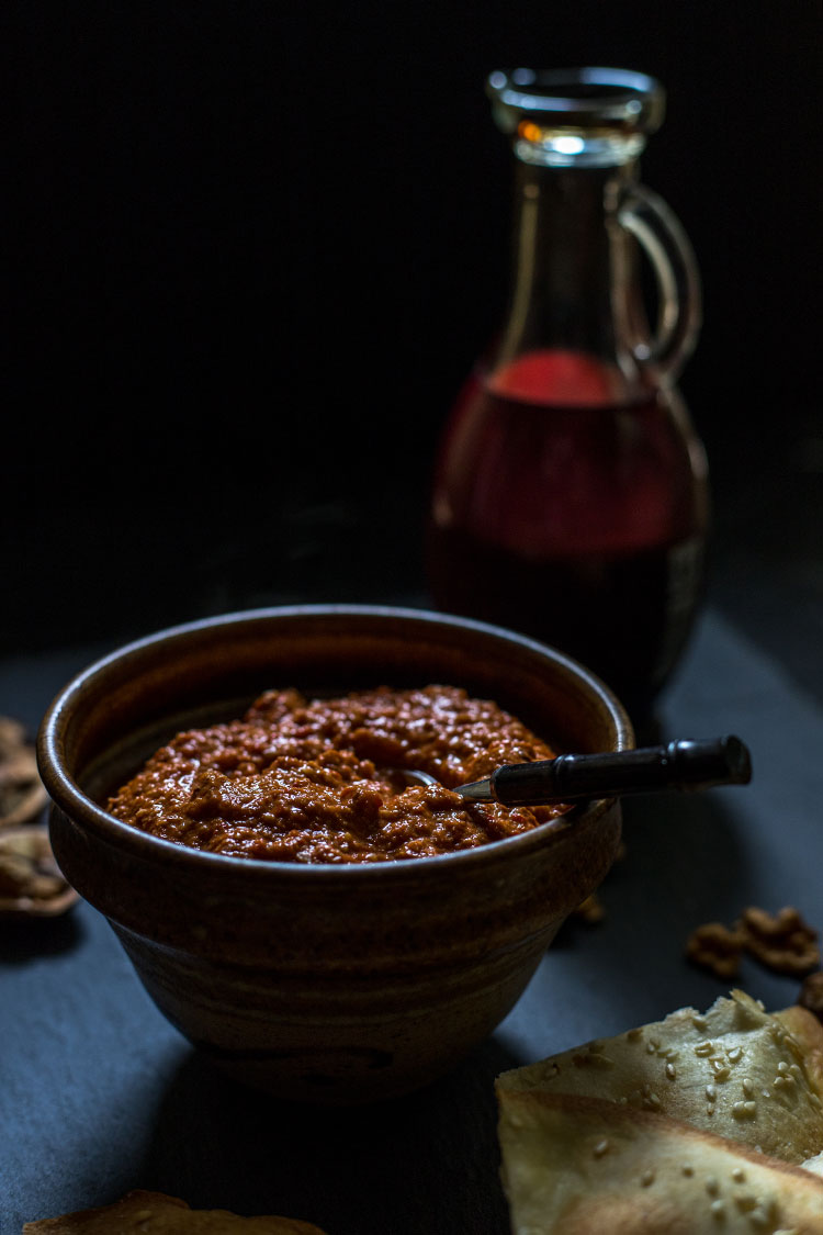 Muhammara red pepper and walnut dip, pictured with a bottle of pomegranate molasses. Vegan and gluten free.