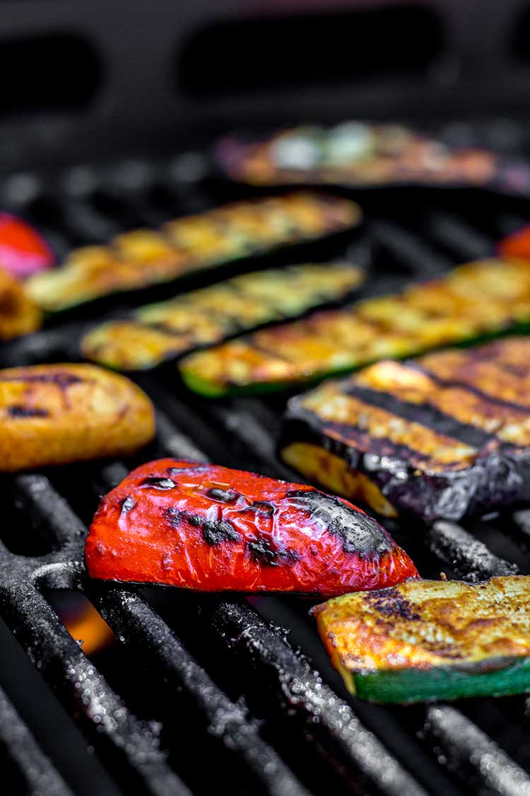 Eggplant, courgette and capsicum being cooked on the barbecue grill.