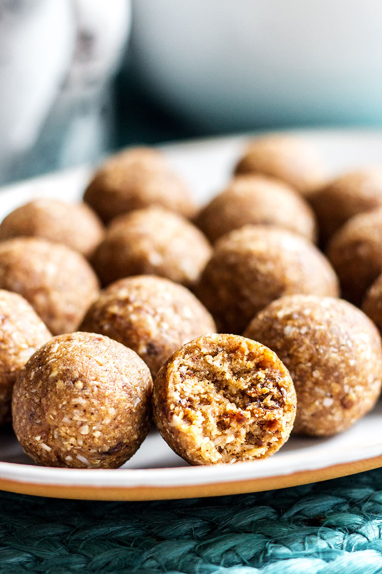 Side view of hot cross bun bliss balls, one with a bite taken from it.