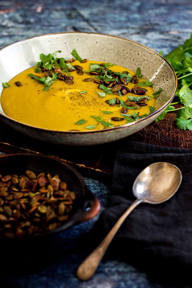 Sweet potato soup with tamari pumpkin seeds (vegan and gluten free). Pictured with a sprinkle of coriander (cilantro) leaves and ready to eat.