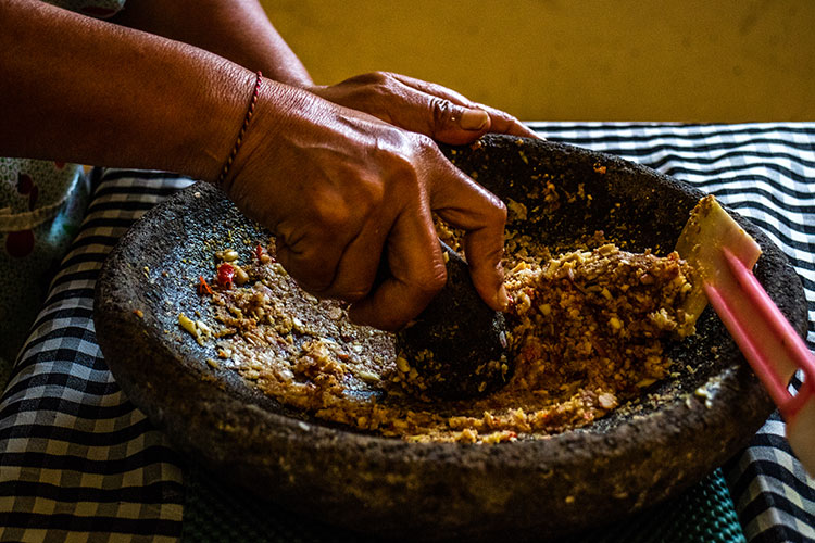 Grinding peanut sauce ingredients in an ulekan, or wide Balinese mortar and pestle.