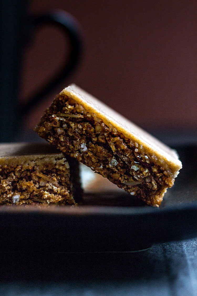 Coffee granola slice (gluten free and vegan), served with a cup of coffee.