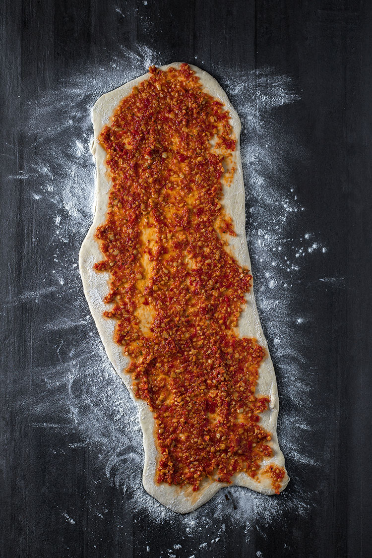 Bread dough rolled into a rectangle and smothered in red pesto.