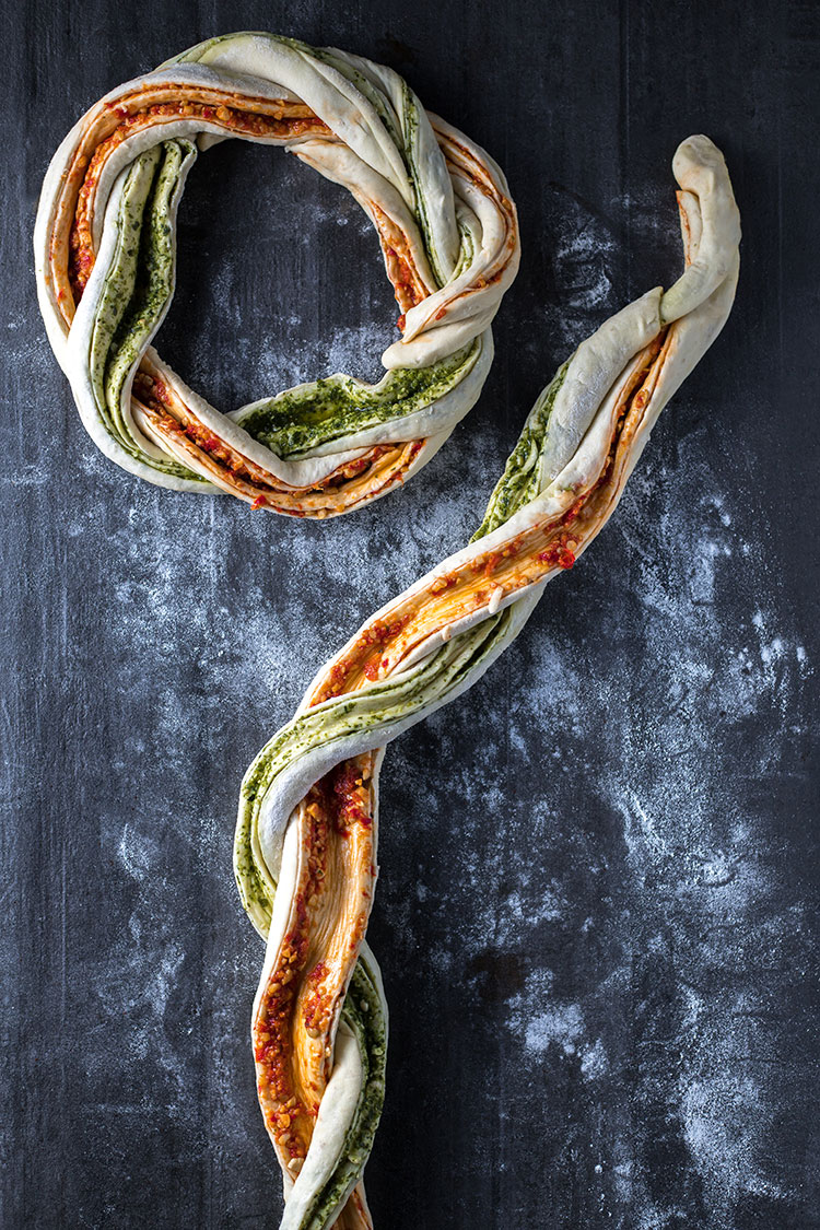 Snakes of pesto filled bread dough twisted together and formed into a bread wreath.