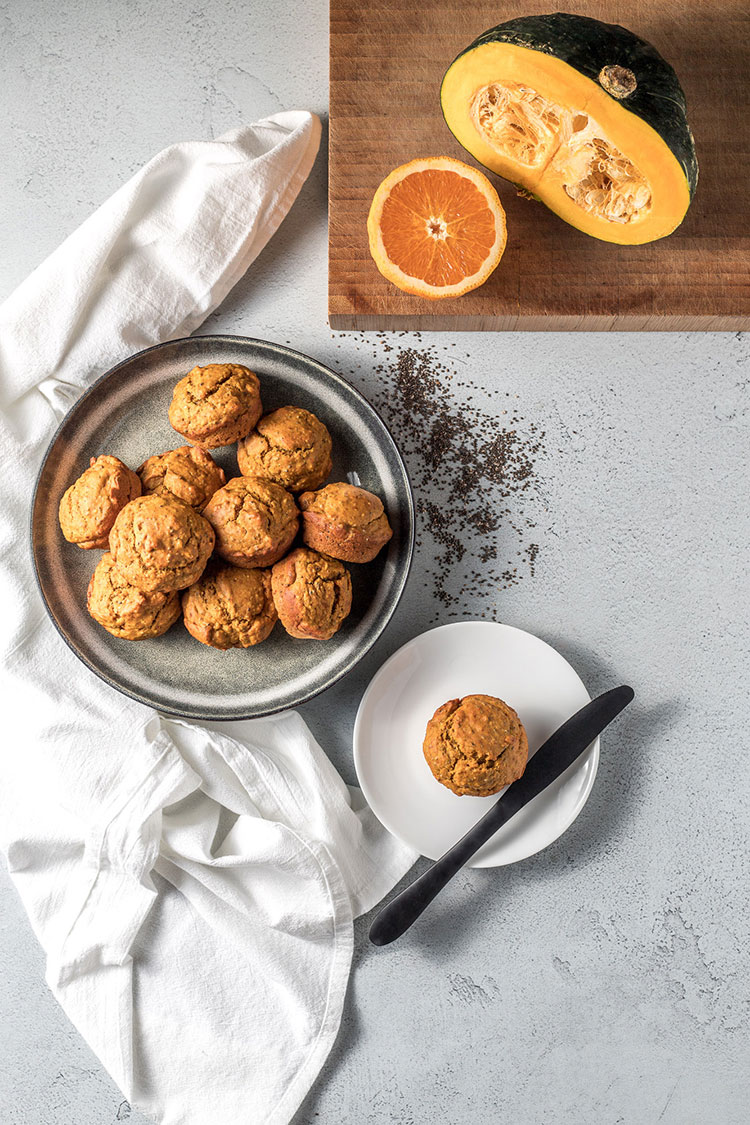 Pumpkin, orange and chia seed muffins on a counter top, pictured alongside a cut pumpkin and half an orange. Vegan.