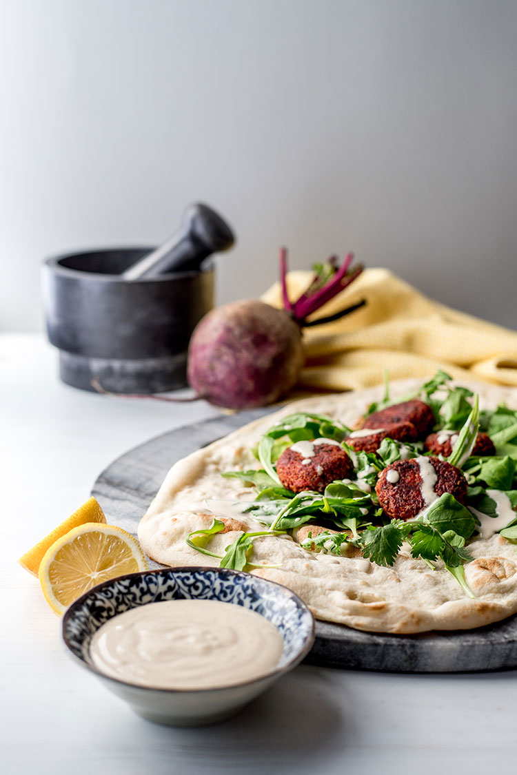 Beetroot falafel with tahini sauce (vegan and gluten free), pictured with salad greens and flat bread.