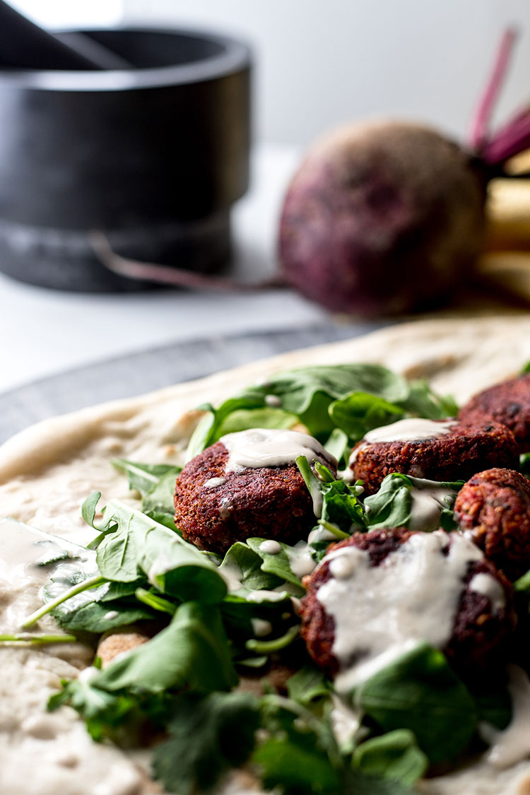 Close up photo of beetroot falafel drizzled with simple tahini sauce.