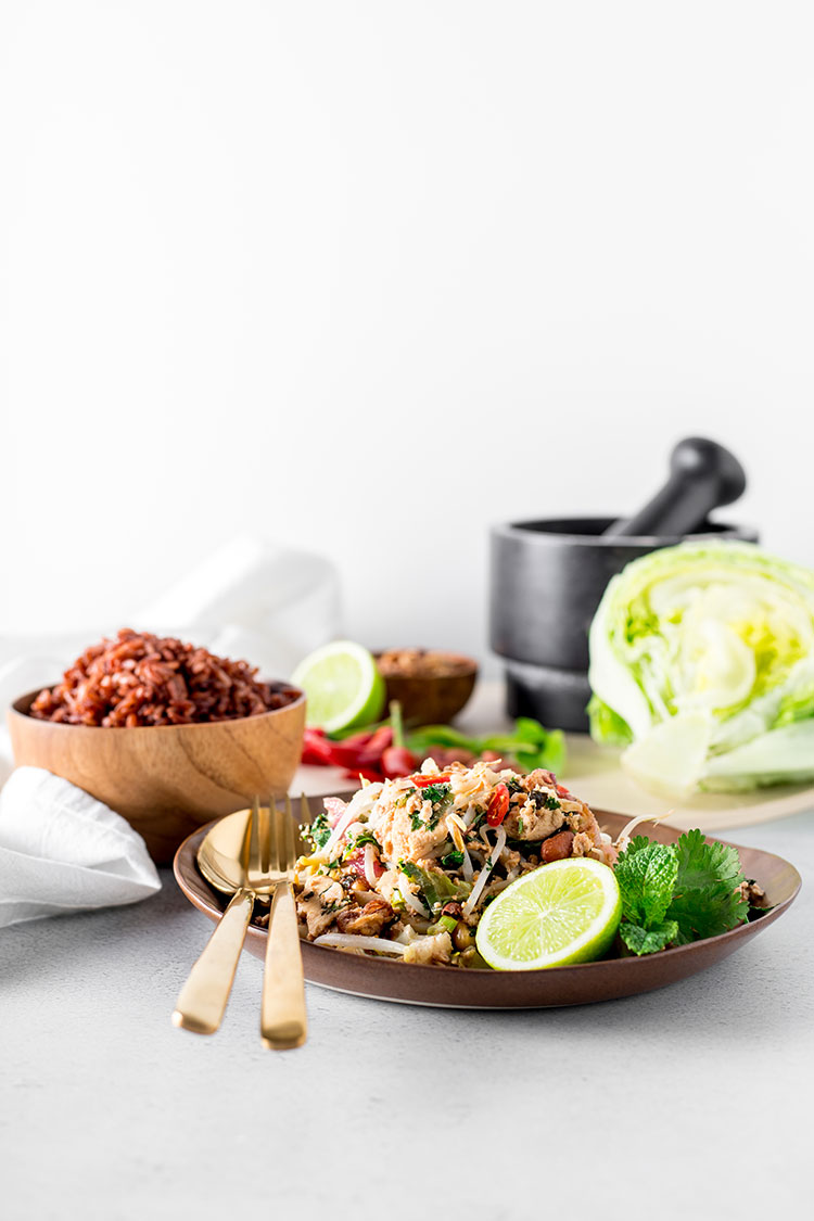 Cauliflower, peanut and tofu larb pictured with red rice, iceburg lettuce and limes.