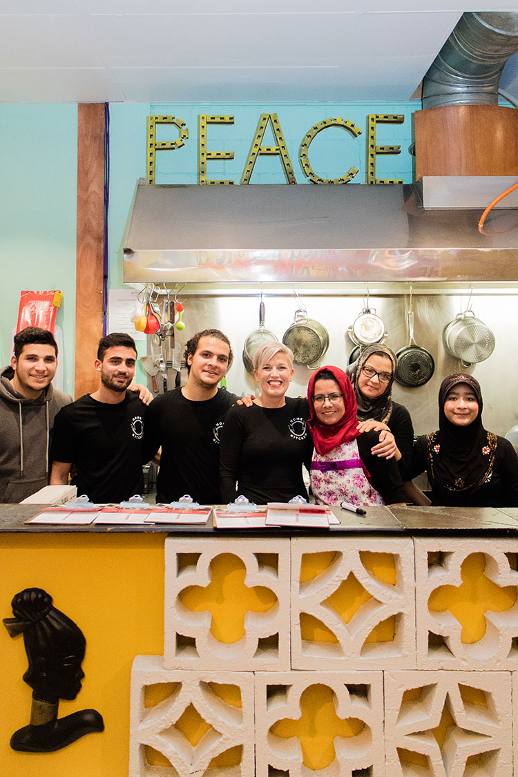 Tania Jones and the team at Home Kitchen, standing in a commercial kitchen under a sign saying 'Peace'.