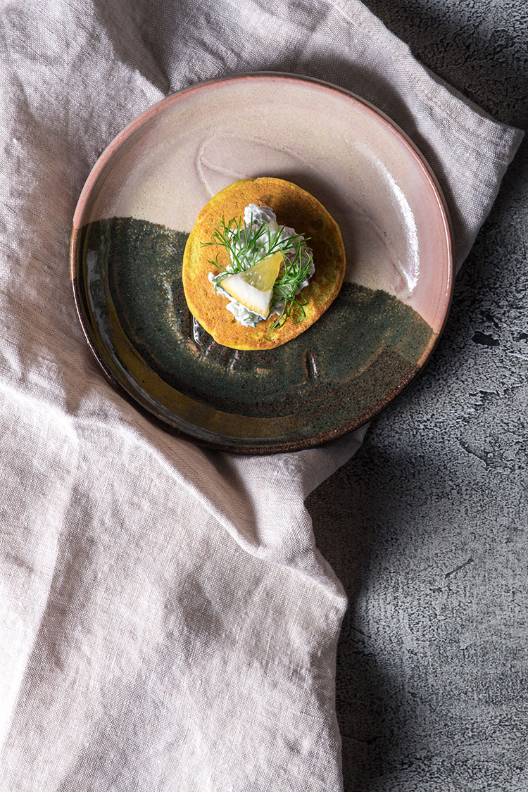 A single spiced vegan blini on a serving plate, sitting on top of a linen napkin.
