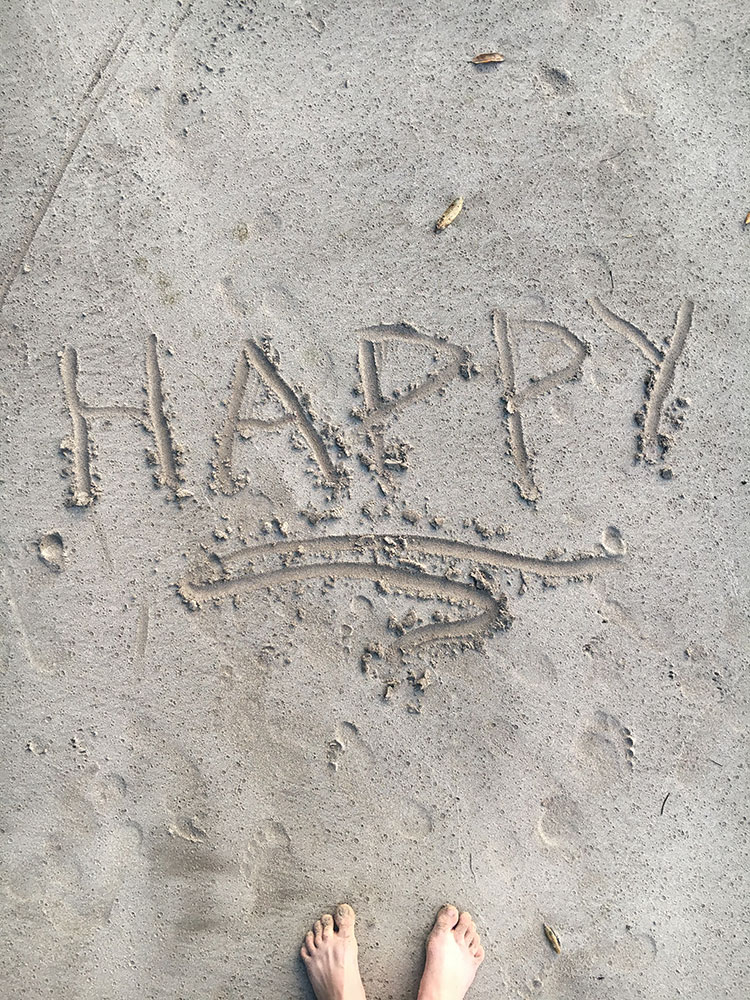 The word happy, written in the sand.