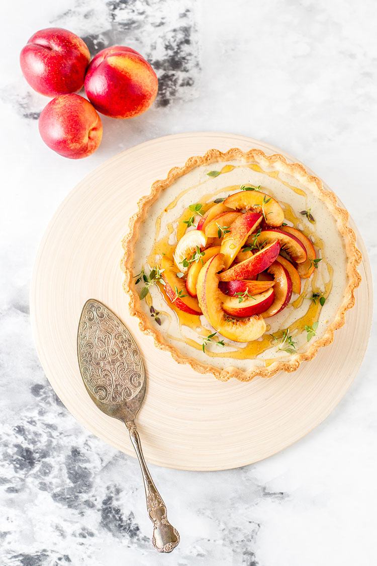 A vegan custard tart sitting on a chopping board. The tart is topped with sliced nectarines, drizzled with honey and sprinkled with fresh thyme leaves.