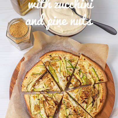 A pizza cut into six pieces sitting on a chopping board. The pizza is topped with white sauce, zucchini ribbons, pine nuts and vegan parmesan sprinkle.
