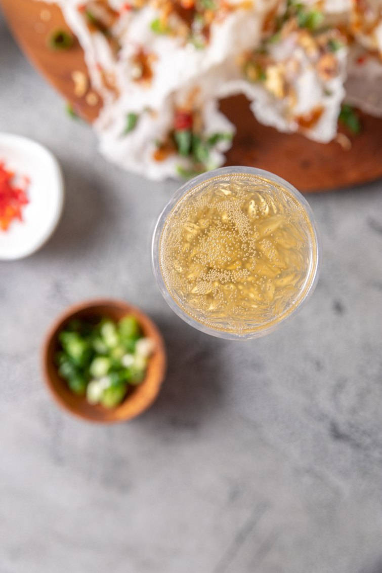 A glass of sparkling wine sitting next to a platter of Vietnamese rice paper crisps.