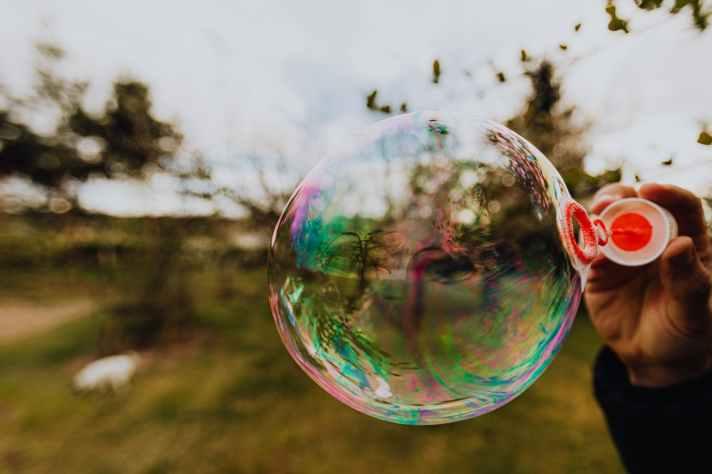 crop person blowing big soap bubble