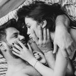 foto preta e branca de um casal deitados na cama