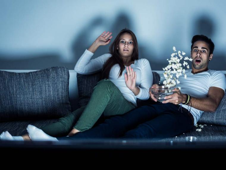 homem e mulher assistindo filme de terror juntos comendo pipoca