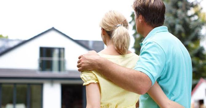 casal olhando a casa que comprou