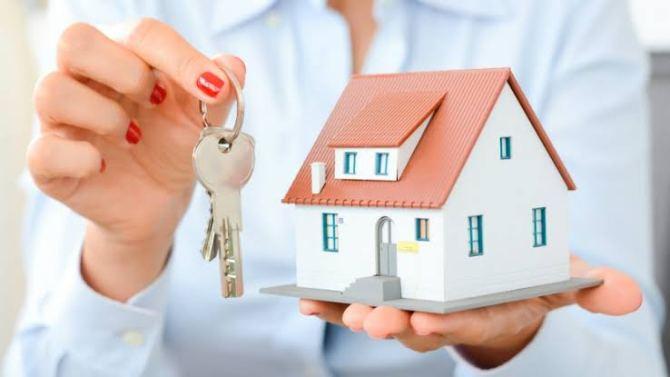 mulher segurando a maquete de uma casa e uma chave