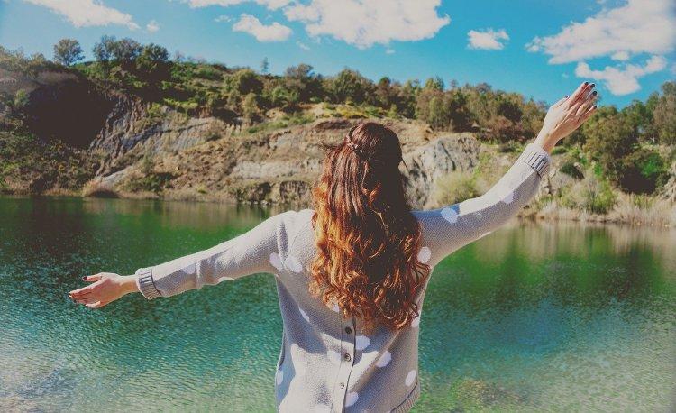 mulher feliz comemorando mais um dia de vida na natureza