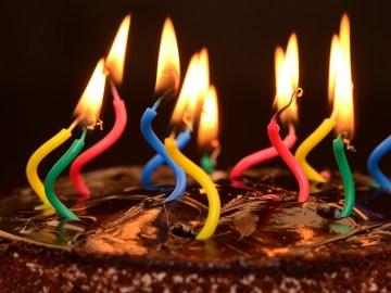 bolo de aniversário com velas coloridas e tortas