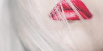 mulher de cabelos brancos e batom vermelho mostrando o poder feminino