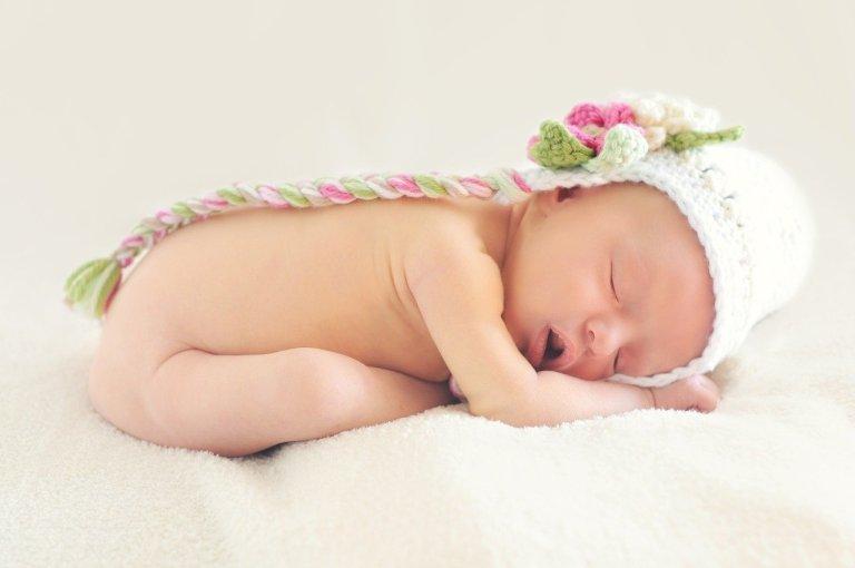bebê menina dormindo com uma toquinha na cabeça