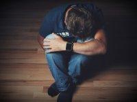 homem sentado no chão chorando e triste