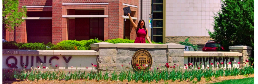 Picture of a QU graduate in front of the school